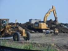 Leveler and Backhoe on site